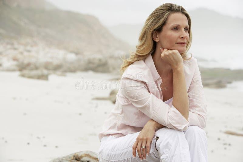 Mulher pensativa que olha ausente ao sentar-se na rocha na praia fotografia de stock royalty free