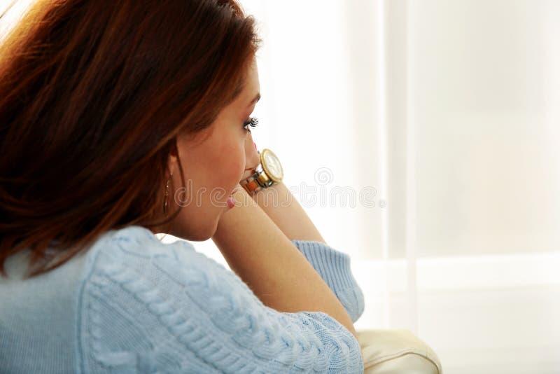 Mulher pensativa que olha na janela imagem de stock