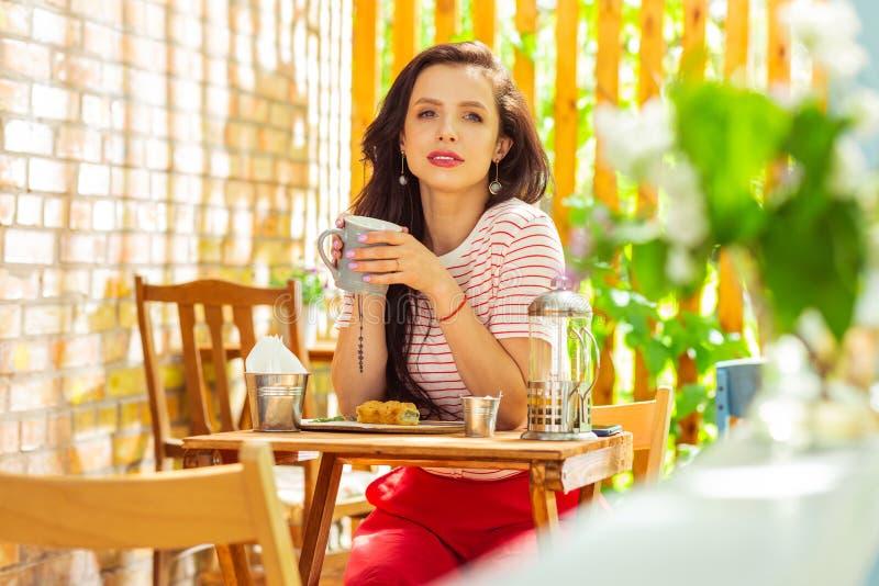 Mulher pensativa que passa sua manhã em um café foto de stock