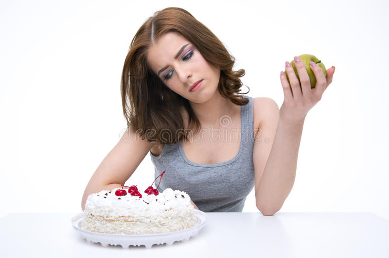 Mulher pensativa que senta-se na tabela com maçã fotografia de stock royalty free