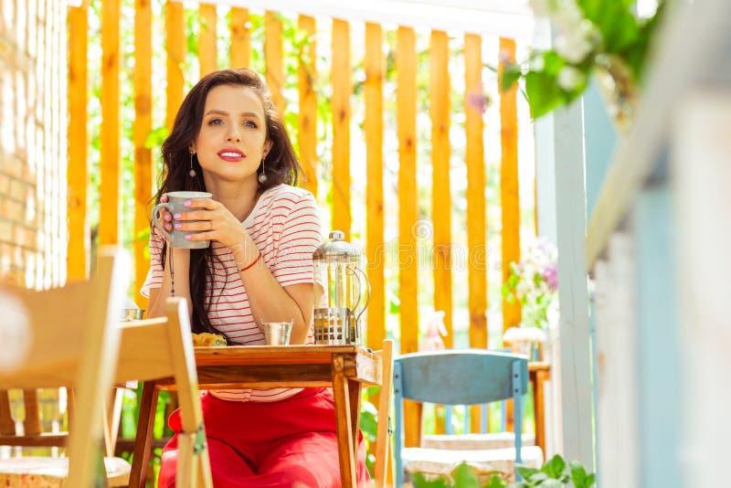 Mulher pensativa que senta-se na tabela do café imagens de stock