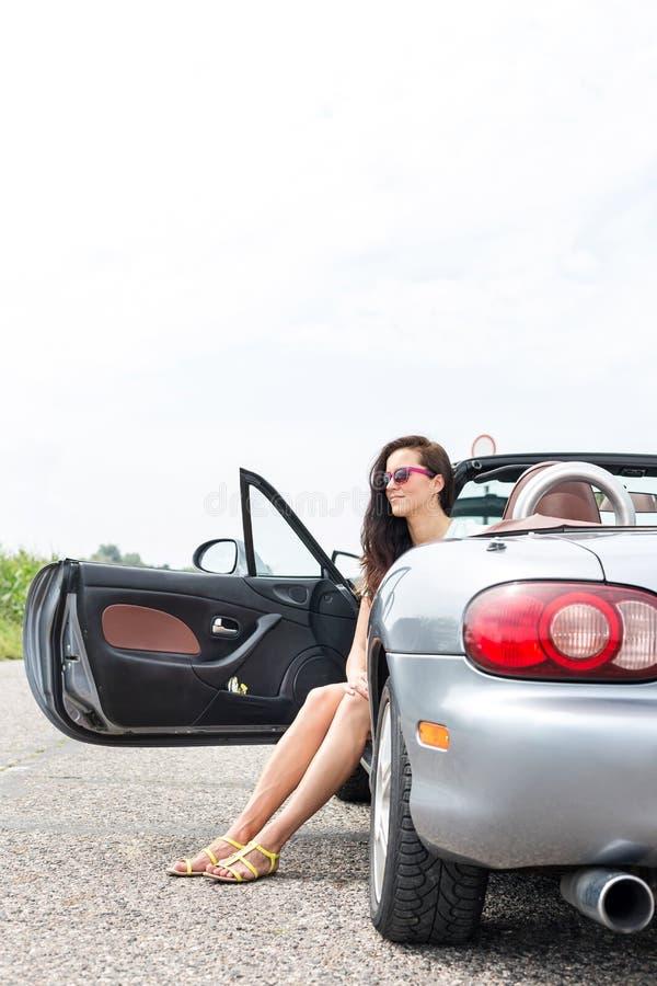 Mulher pensativa que senta-se no convertible na estrada secundária contra o céu claro foto de stock
