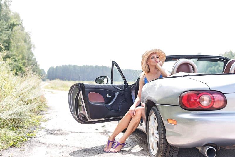 Mulher pensativa que senta-se no convertible na estrada secundária contra o céu claro imagem de stock royalty free