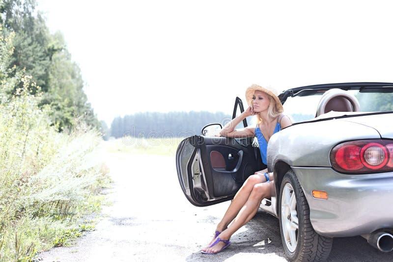 Mulher pensativa que senta-se no convertible na estrada secundária contra o céu claro fotos de stock