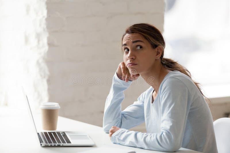 Mulher pensativa que senta-se no local de trabalho, pensando aproximadamente difícil fotos de stock