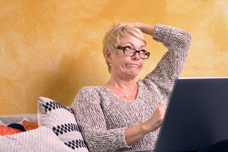 Mulher pensativa que senta-se no sofá com portátil imagem de stock