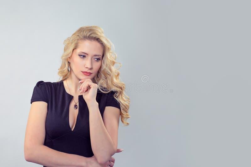 Mulher pensativa sensual no vestido preto imagens de stock royalty free