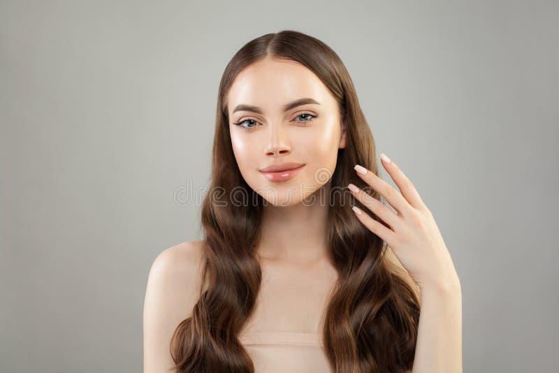 Mulher perfeita com cabelo saudável longo, pele clara e mão com pregos manicured Conceito dos cuidados com a pele e dos cuidados  foto de stock royalty free