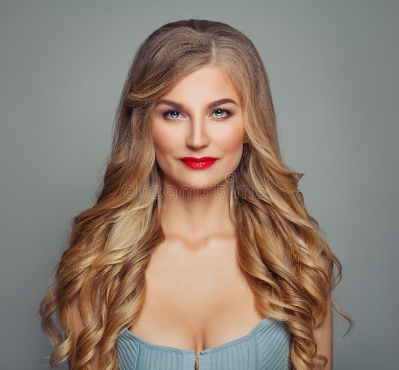 Mulher perfeita do cabelo louro com composição vermelha dos bordos e corte de cabelo encaracolado Retrato da beleza foto de stock
