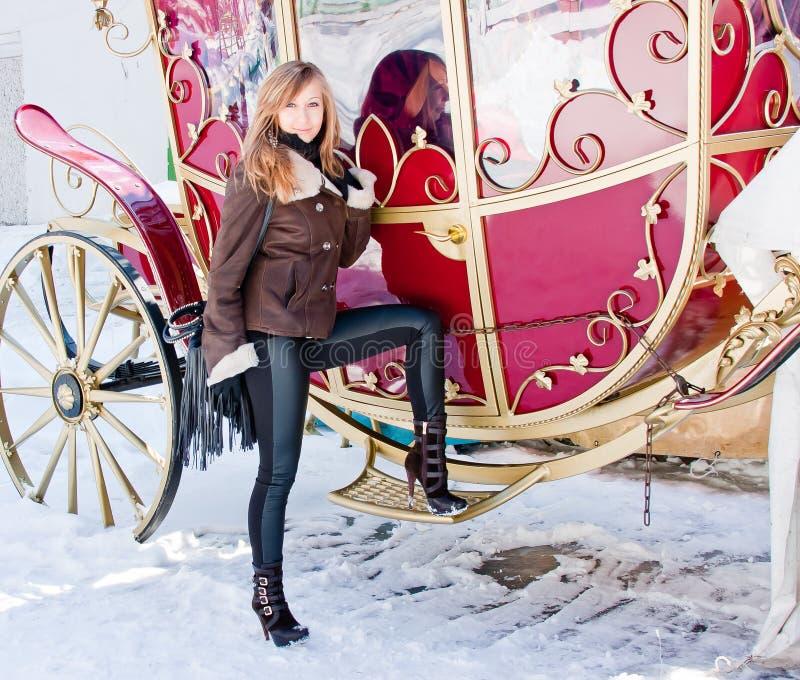 Mulher perto de um ônibus em um parque do inverno fotografia de stock