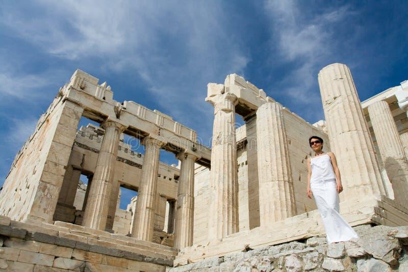 Mulher perto do Acropolis Atenas das colunas de Propylaea fotografia de stock royalty free