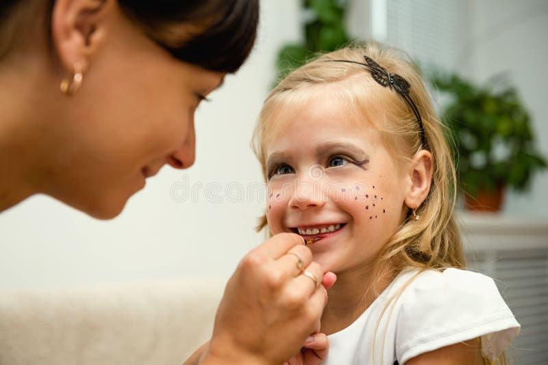 A mulher pinta a cara de uma criança para o feriado fotos de stock royalty free