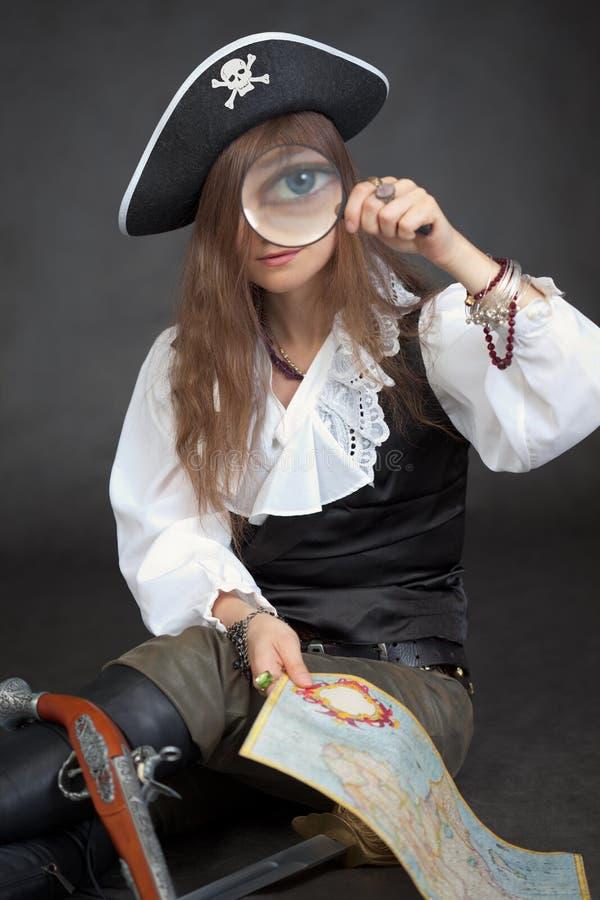 Mulher-pirata com mapa do mar e vidro do magnifier fotografia de stock royalty free