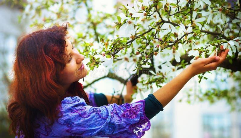 Mulher poética nova com tempo da árvore da magnólia na primavera Mulher que guardara a flor fotos de stock royalty free