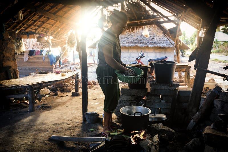 A mulher pobre do aldeão cozinha a refeição sob o abrigo básico fotos de stock royalty free