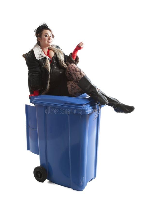 Mulher pobre perto do balde do lixo imagem de stock