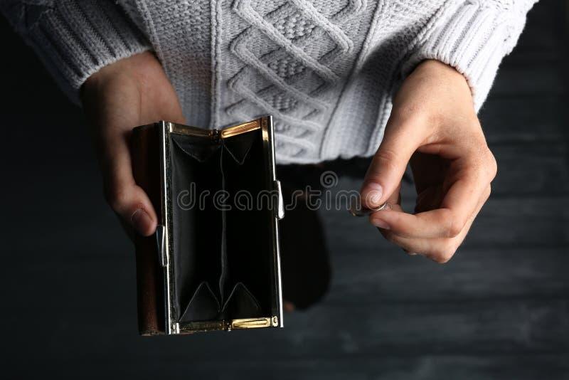 Mulher pobre que guarda a carteira e a moeda vazias imagens de stock