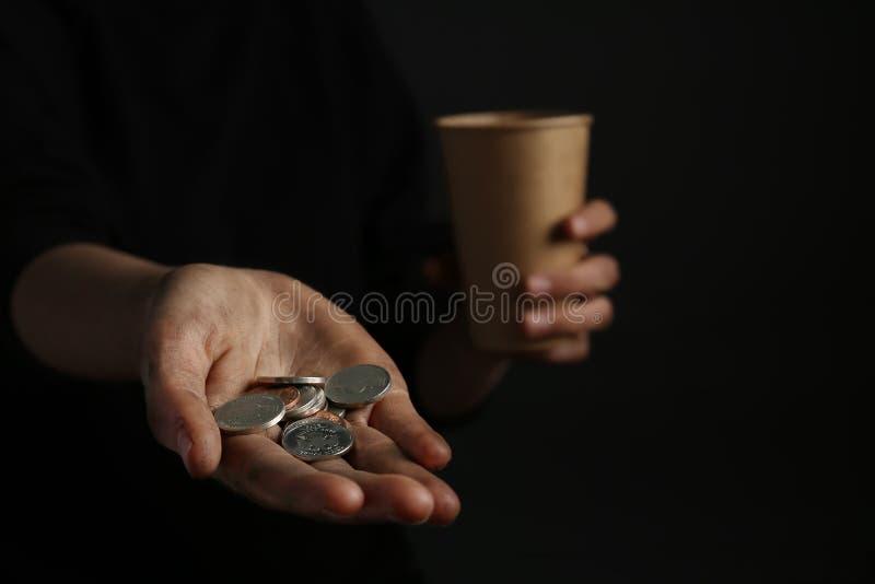 Mulher pobre que guarda moedas no fundo escuro imagem de stock