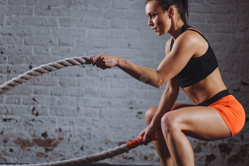 A mulher poderosa malha com cordas da batalha no gym imagens de stock royalty free