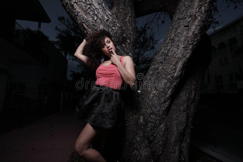 Mulher por uma árvore na noite imagens de stock royalty free