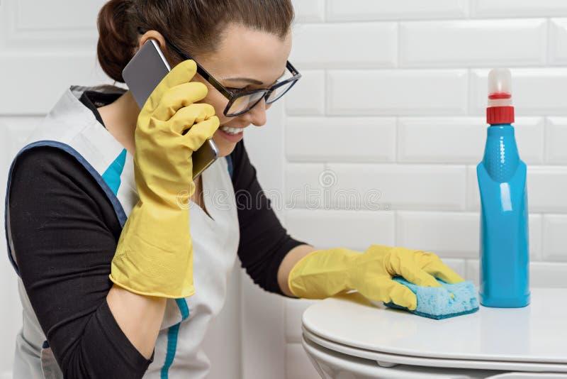 Mulher positiva adulta que faz a limpeza com detergentes Mulher nos vidros, uniforme profissional no banheiro, toaletes, riso da  fotos de stock royalty free