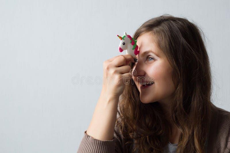 A mulher positiva alegre guarda um unicórnio do brinquedo perto de sua testa foto de stock