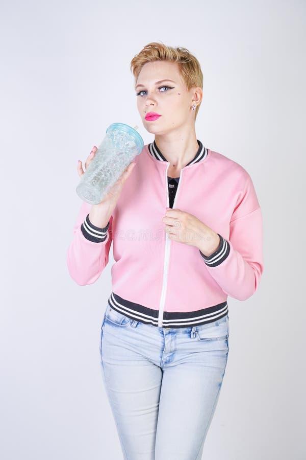 Mulher positiva bonita do cabelo curto do tamanho com o copo de água azul revestimento e calças de brim vestindo do rosa do espor imagem de stock