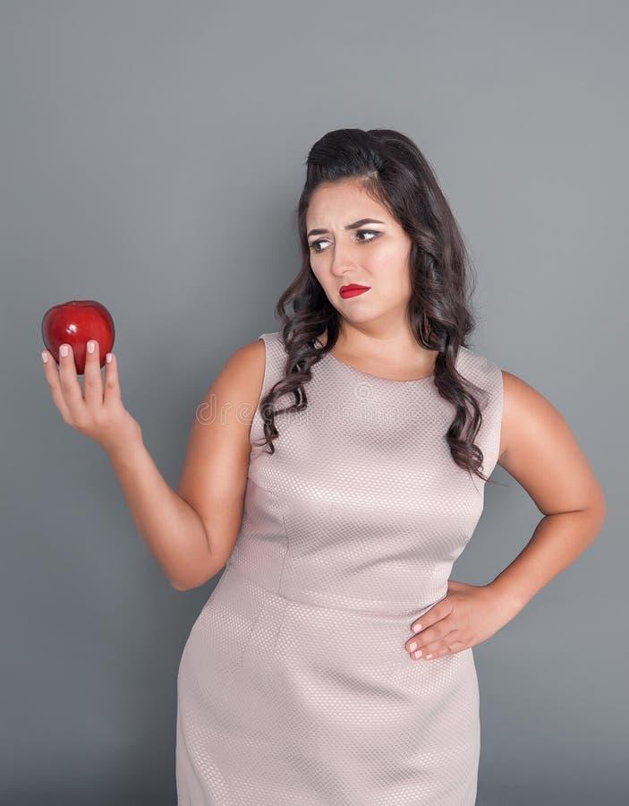 A mulher positiva bonita do tamanho não quer a maçã no cinza Concep da dieta fotos de stock