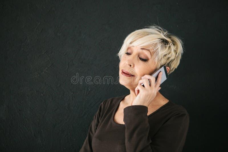 Mulher positiva bonita madura que fala no telefone celular fotografia de stock