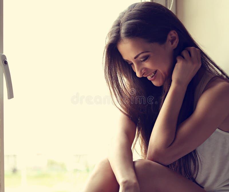 Mulher positiva de sorriso bonita que senta-se perto da janela e do gabinete imagens de stock