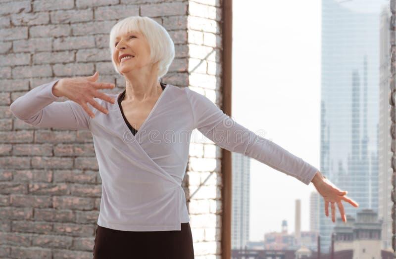 Mulher positiva do envelhecimento que domina habilidades da dança na lição fotografia de stock