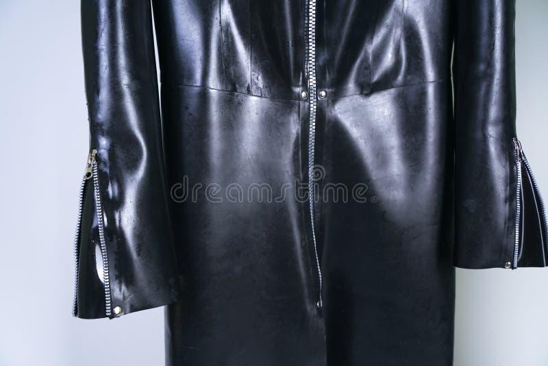 Mulher positiva do tamanho no terno do látex e botas de couro na capa de chuva de borracha pesada grossa no fundo branco no estúd fotografia de stock