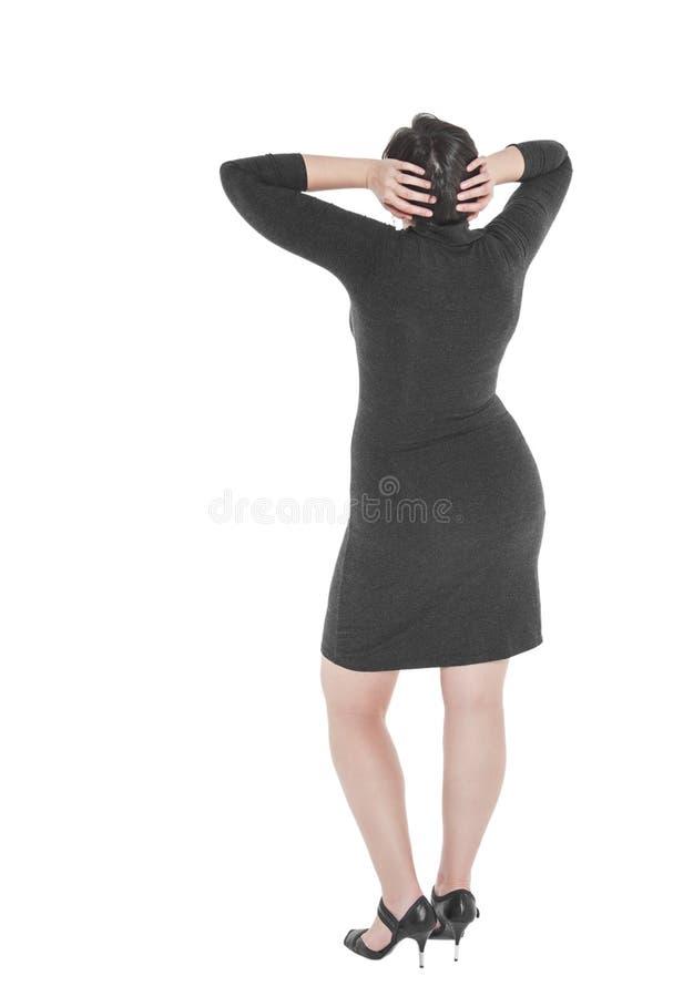 Mulher positiva do tamanho que está e que olha em algo Pose traseira fotografia de stock royalty free