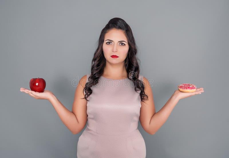 Mulher positiva do tamanho que faz a escolha entre o alimento saudável e insalubre fotos de stock royalty free