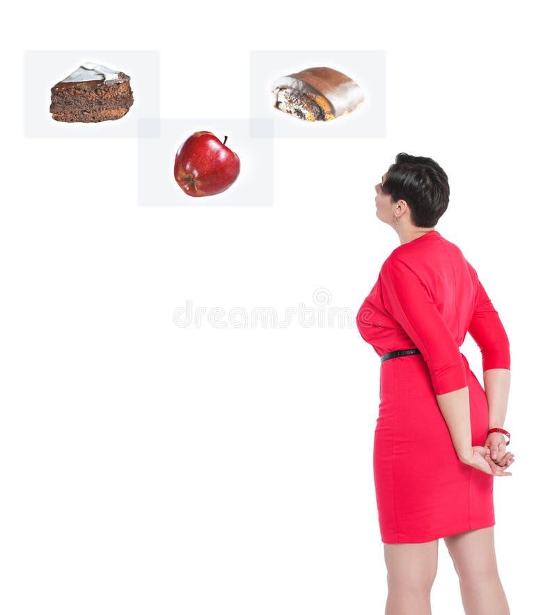 Mulher positiva do tamanho que faz a escolha entre o alimento saudável e insalubre fotografia de stock