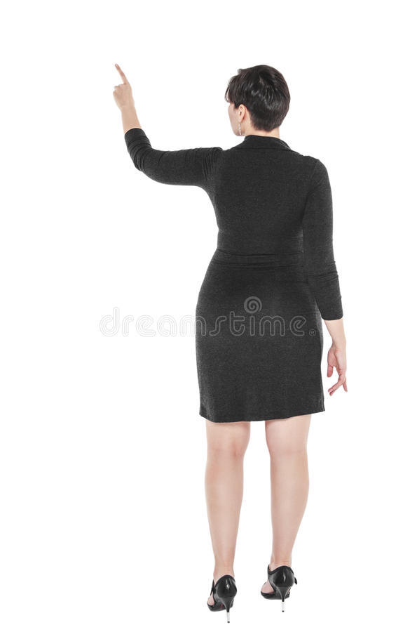 Mulher positiva do tamanho que mostra em algo pelo dedo Pose traseira imagens de stock royalty free