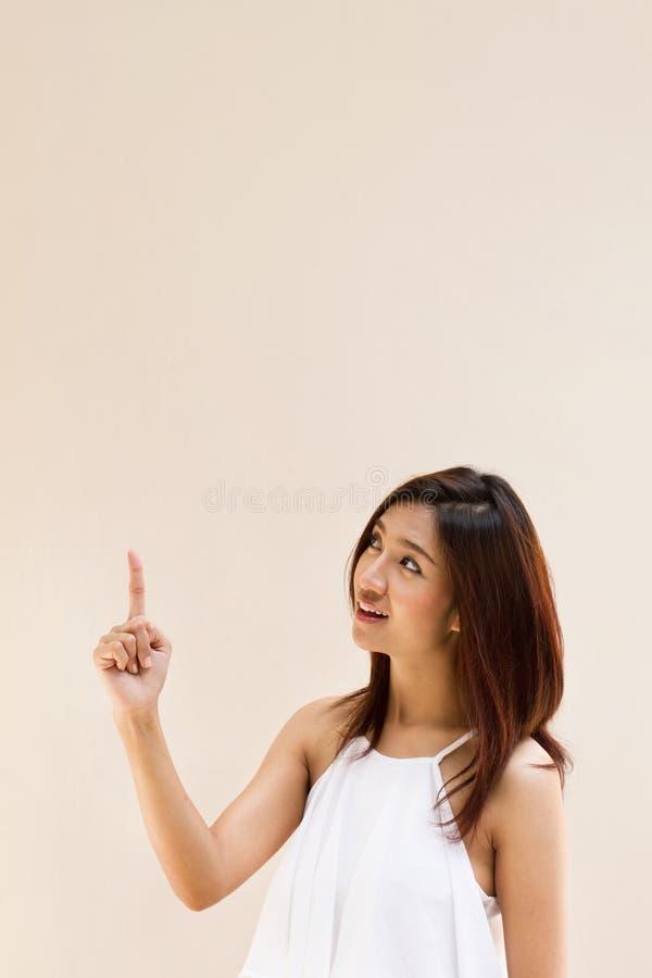 Mulher positiva feliz de sorriso bonita que aponta sua mão acima foto de stock royalty free