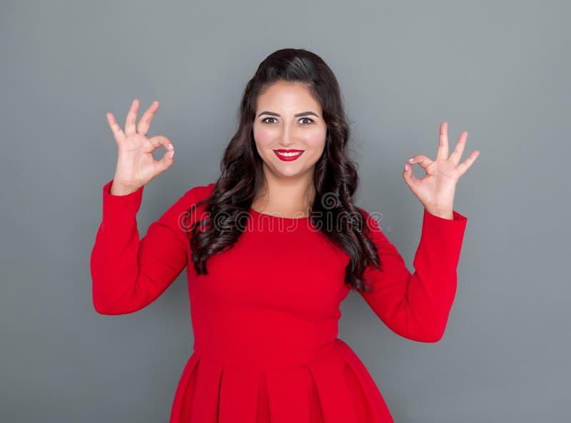 Mulher positiva feliz do tamanho no vestido vermelho com gesto aprovado no cinza imagens de stock