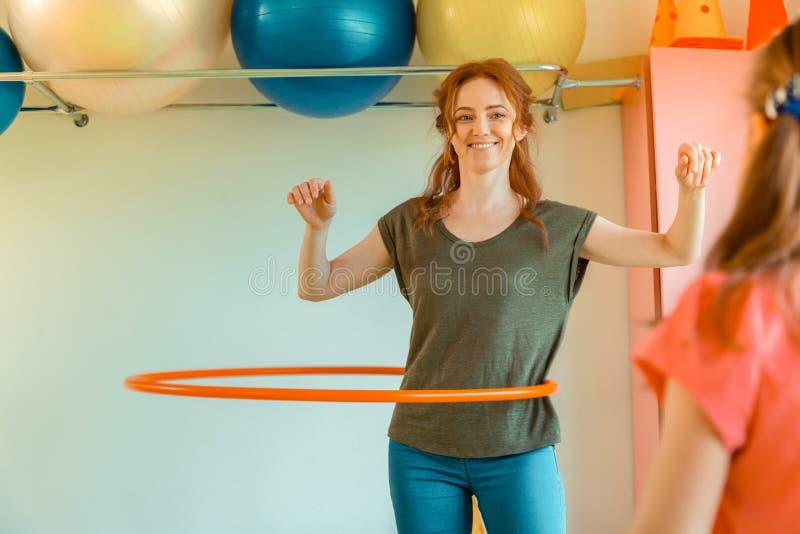 Mulher positiva feliz que gerencie uma aro do hula imagem de stock