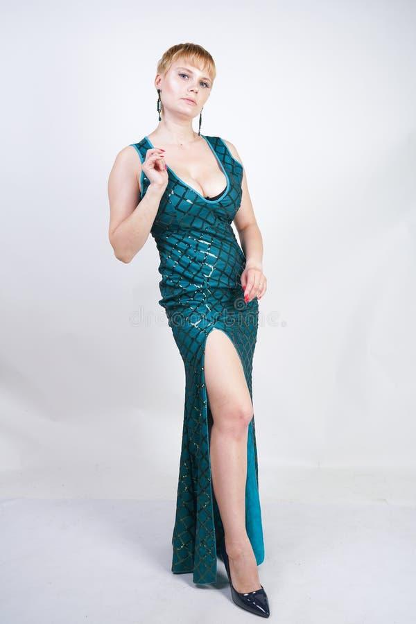 Mulher positiva nova encantador do tamanho com o cabelo louro curto vestido em um vestido longo luxuoso do verde da noite com lan imagem de stock royalty free