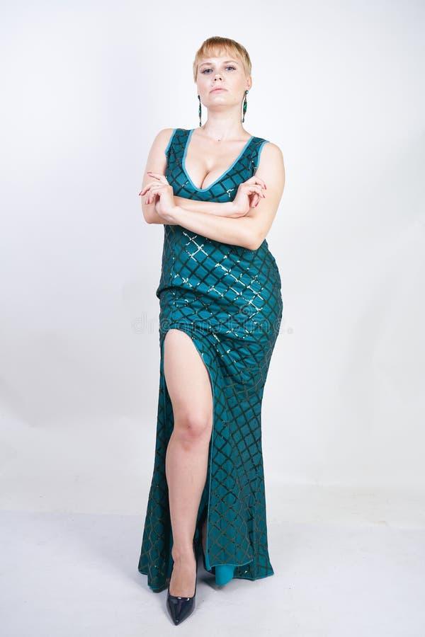 Mulher positiva nova encantador do tamanho com o cabelo louro curto vestido em um vestido longo luxuoso do verde da noite com lan fotos de stock royalty free