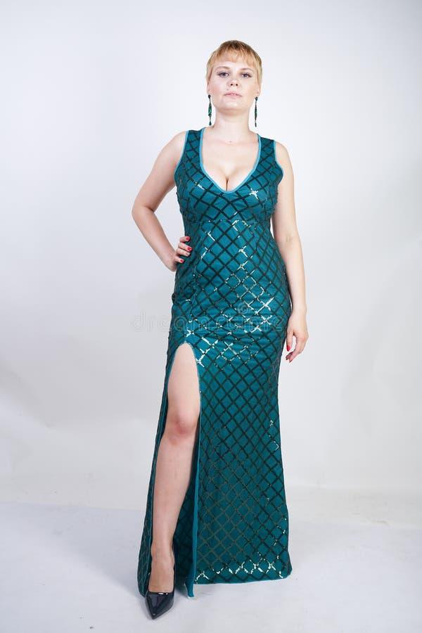 Mulher positiva nova encantador do tamanho com o cabelo louro curto vestido em um vestido longo luxuoso do verde da noite com lan imagens de stock royalty free