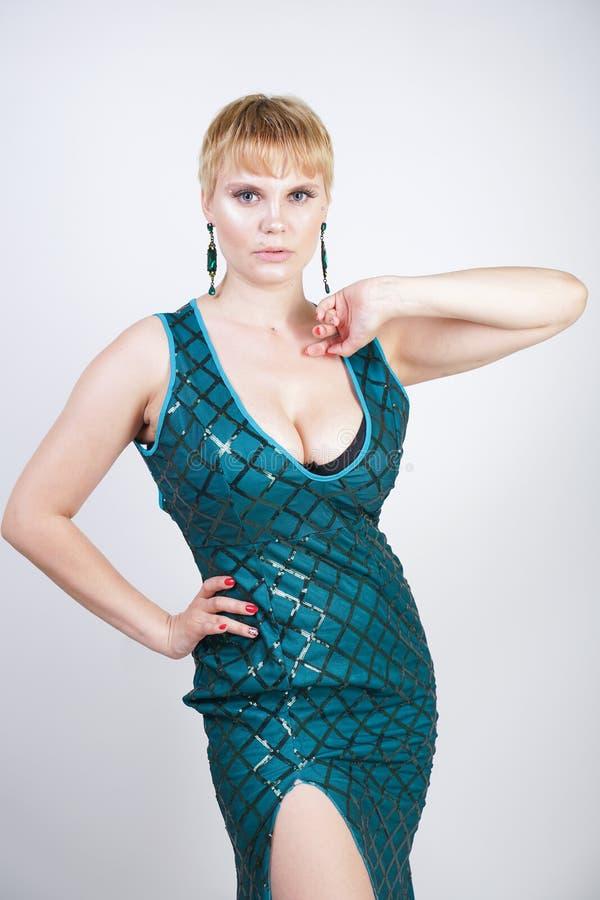 Mulher positiva nova encantador do tamanho com o cabelo louro curto vestido em um vestido longo luxuoso do verde da noite com lan fotografia de stock