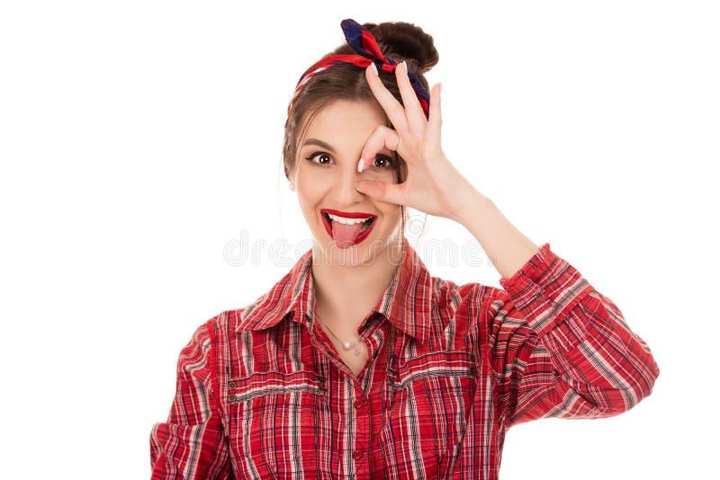 Mulher positiva que olha a câmera através da mão no gesto aprovado foto de stock