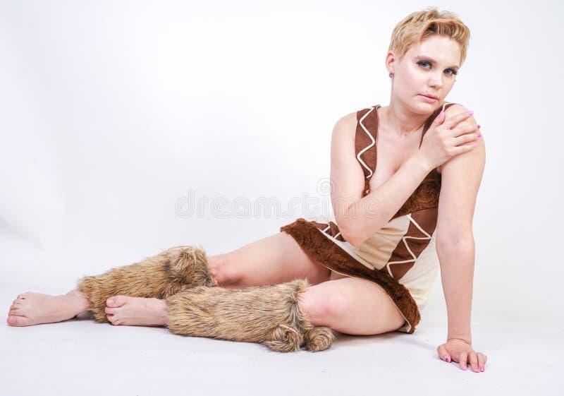 Mulher positiva quente do tamanho no traje do carnaval da pele do homem primitivo no fundo branco no estúdio uma menina selvagem  imagens de stock royalty free