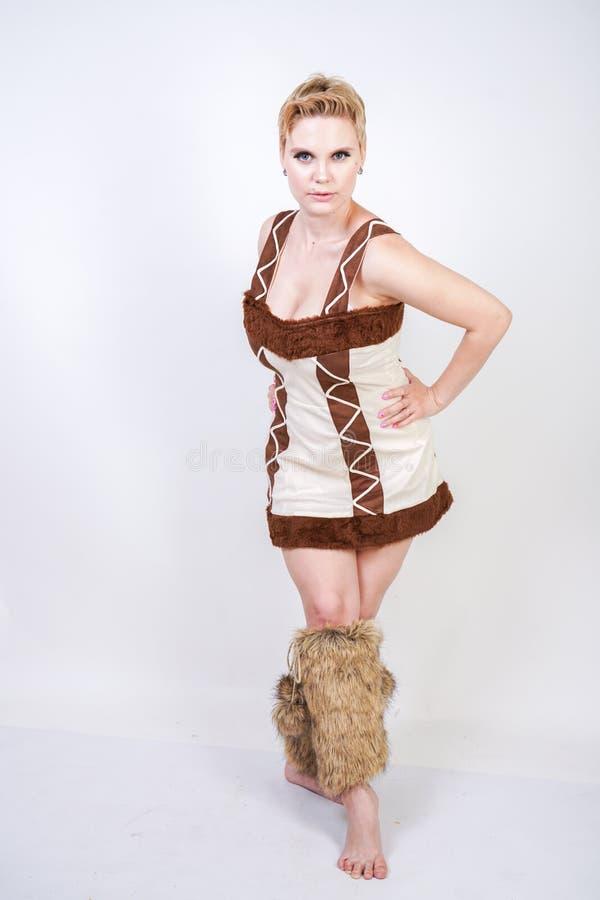 Mulher positiva quente do tamanho no traje do carnaval da pele do homem primitivo no fundo branco no estúdio uma menina selvagem  fotografia de stock