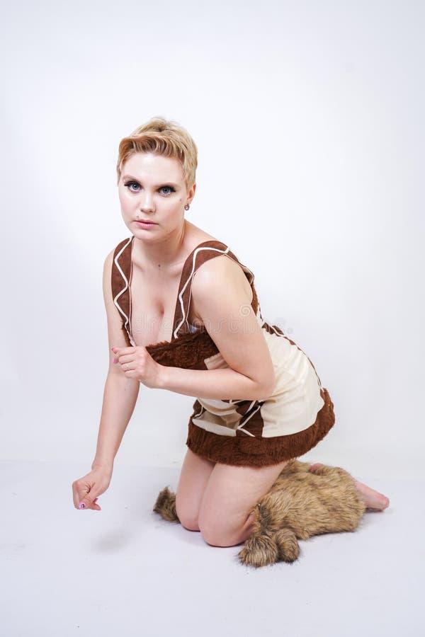 Mulher positiva quente do tamanho no traje do carnaval da pele do homem primitivo no fundo branco no estúdio uma menina selvagem  imagens de stock
