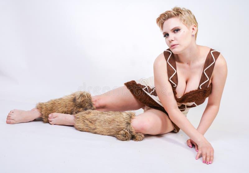 Mulher positiva quente do tamanho no traje do carnaval da pele do homem primitivo no fundo branco no estúdio uma menina selvagem  foto de stock royalty free