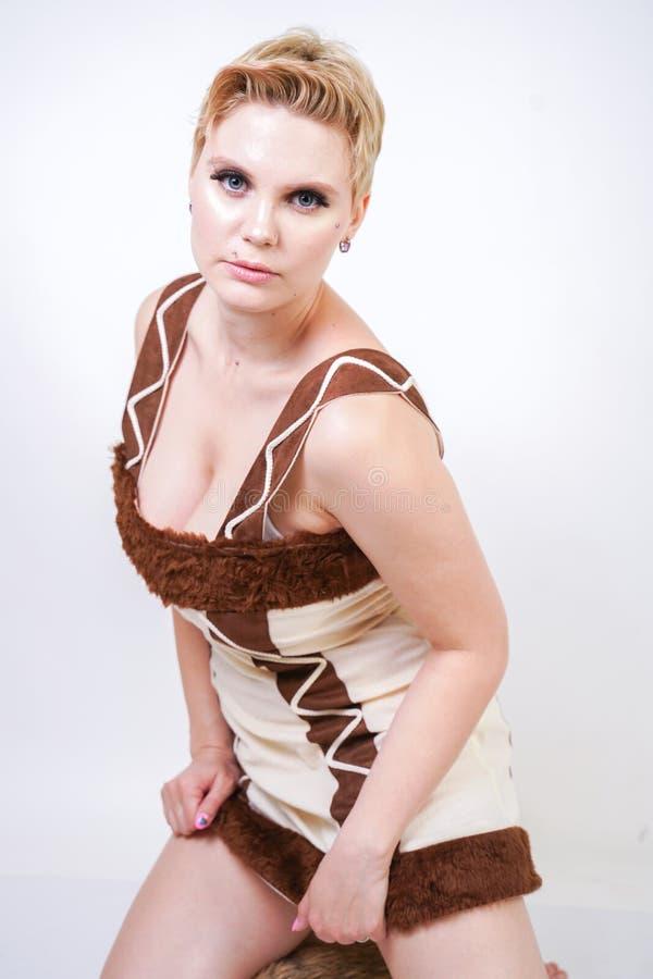 Mulher positiva quente do tamanho no traje do carnaval da pele do homem primitivo no fundo branco no estúdio uma menina selvagem  imagem de stock royalty free