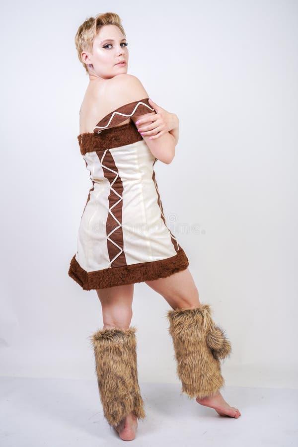 Mulher positiva quente do tamanho no traje do carnaval da pele do homem primitivo no fundo branco no estúdio uma menina selvagem  fotos de stock royalty free